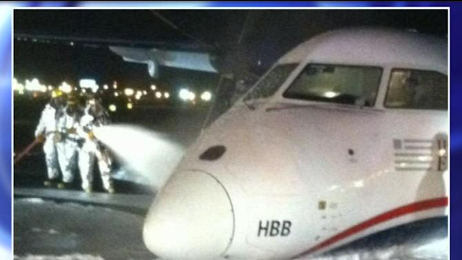 In this image taken from video and provided to WABC TV News by an airport source, emergency personnel spray foam on the fuselage of a US Airways Express commuter plane after it made a belly landing at Newark Liberty International Airport, Saturday, May 18, 2013, in Newark, N.J. The turboprop plane reportedly left Philadelphia shortly before 11 p.m., Friday, and landed safely at Newark with its landing gear retracted at about 1 a.m., Saturday. There were no injuries. (AP Photo/WABC TV News) MANDATORY CREDIT; NYC OUT