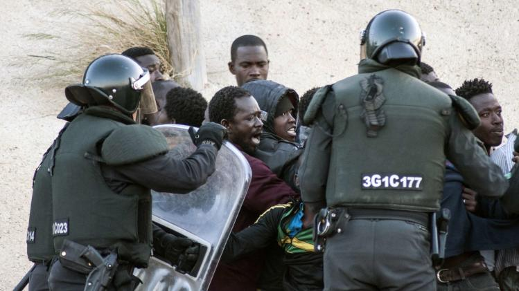 African migrants are surrounded by Spanish Civil Guard officers after descending from the top of a border post between Morocco and Spain's north African enclave of Melilla during their latest attempt to cross into Spanish territory