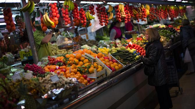 FILE - In this Thursday Jan. 17, 2013 file photo, a woman buys fruit at a market in Barcelona, Spain. Mediterranean diets have long been touted as heart-healthy, but that's based on observational studies. Now, one of the longest and most scientific tests suggests this style of eating can cut the chance of suffering heart-related problems, especially strokes, in older people at high risk of them. The study lasted five years and involved about 7,500 people in Spain. Results were published online Monday, Feb. 25, 2013 by the New England Journal of Medicine. (AP Photo/Emilio Morenatti)
