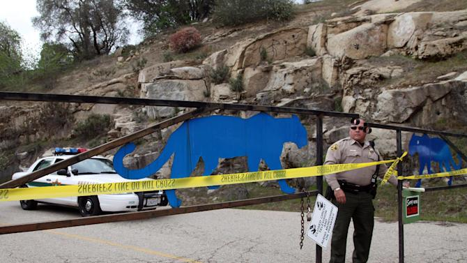 An officer guards the gate near at the entrance of Cat Haven, the exotic animal park in central California where a 26-year old female volunteer intern was killed by a lion, Wednesday, March 6, 2013 in Dunlap, Calif. (AP Photo/Gosia Wozniacka)