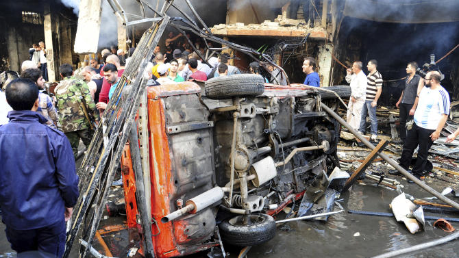 In this photo released by the Syrian official news agency SANA, Syrian citizens and security forces, gather next of a damaged car  that was destroyed by a car bomb, at Jaramana neighborhood, in Damascus, Syria, Monday Oct. 29, 2012. A Syrian government official says a car bomb in a Damascus suburb has killed 10 people. The official said the blast on Monday in Jaramana also wounded 41 people and caused heavy damage. He spoke on condition of anonymity because he was not authorized to speak to the media. (AP Photo/SANA)