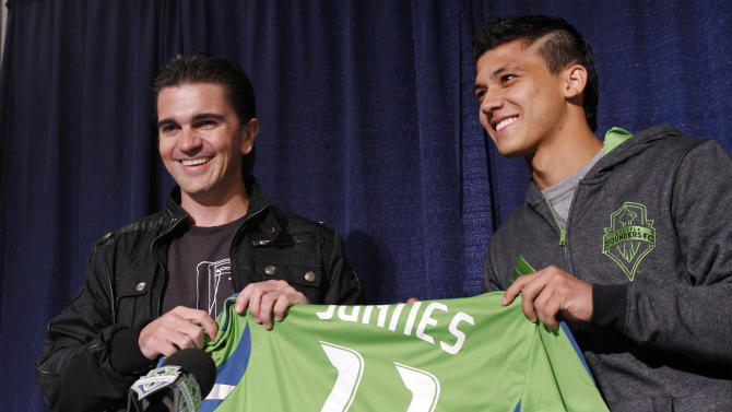 "Colombian singer Juanes, left, is given a Seattle Sounders FC jersey by forward Fredy Montero during a news conference about Juanes upcoming tour Tuesday, March 8, 2011, in Seattle. Juanes kicks-off his world ""P.A.R.C.E. Tour"" Thursday March 10, in Seattle. (AP Photo/Elaine Thompson)"