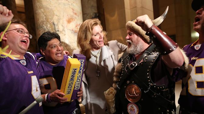 Sen. Julie Rosen, the author of a Minnesota Vikings stadium bill, celebrates the passage of the bill with a few Vikings fans outside the Senate chambers late Tuesday night, May 8, 2012, at the Capitol in St. Paul, Minn. Minnesota lawmakers working out a final Vikings stadium bill are deciding how much money the team should put into the $975 million project. The House is poised to vote Wednesday if a negotiating committee can mesh different bills that passed the Legislature this week. Both bills would raise the Vikings' contribution beyond the $427 million promised. The House voted to make it $532 million, while the Senate bill would set it at $452 million. (AP Photo/Star Tribune, Renee Jones Schneider) ST. PAUL OUT   MINNEAPOLIS-AREA TV OUT  MAGS OUT