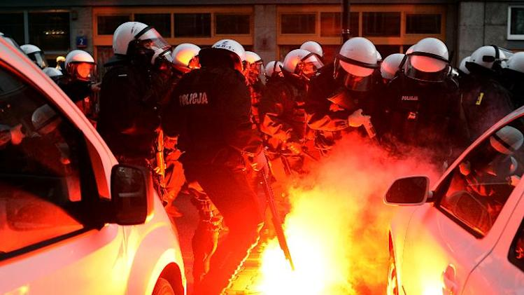 Police put out fires during clashes with far-right protesters during their annual march, which coincides with Poland's national Independence Day, in Warsaw on November 11, 2013