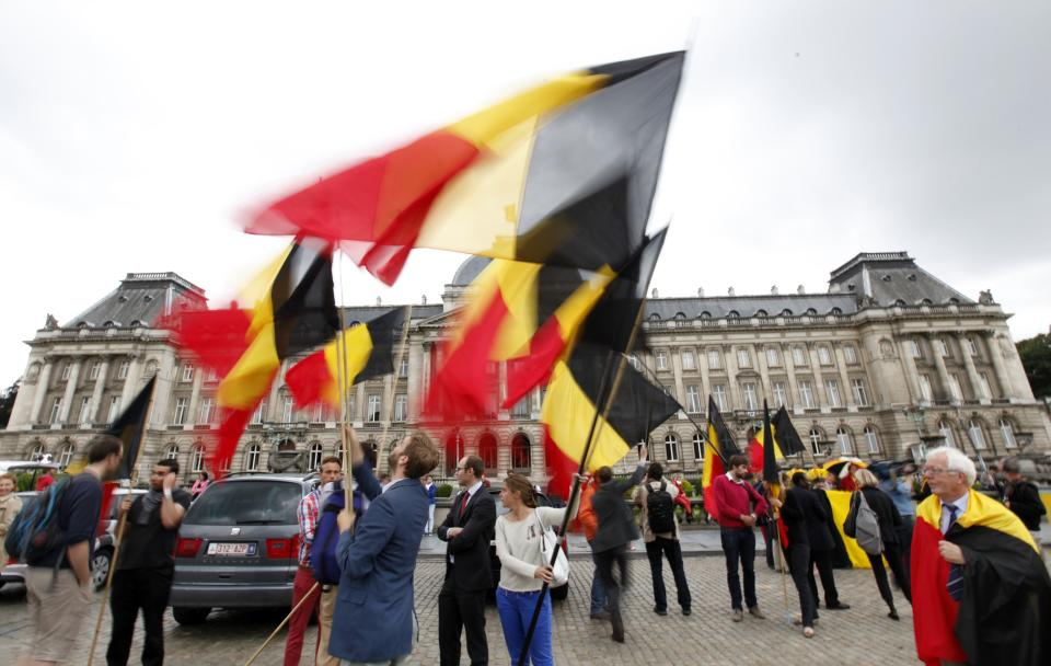 People wave the Belgian flag in front of the Royal Palace downtown Brussels, Wednesday, July 3, 2013. Belgian King Albert has unexpectedly announced that he will step down in favor of his son, Crown Prince Philippe. on July 21, 2013. (AP Photo/Francois Walschaerts)