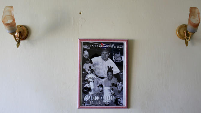 In this April 23, 2013 photo, pictures of Cuba's former pitcher Conrado Marrero hangs on the wall of his home in Havana, Cuba.  Marrero, the world's oldest living former major league baseball player, turns 102 on Thursday, April 25.  In addition to his longevity, the former Washington Senator has much to celebrate this year. After a long wait, he finally received a $20,000 payout from Major League baseball granted to old-timers who played between 1947 and 1979. The money had been held up since 2011 due to issues surrounding the 51-year-old U.S. embargo on Cuba, which prohibits most bank transfers to the Communist-run island. But the payout finally arrived in two parts, one at the end of last year, and the second a few months ago, according to Marrero's family. (AP Photo/Franklin Reyes)