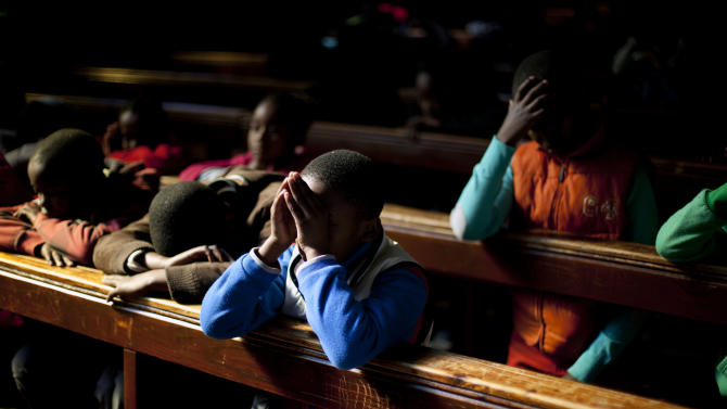 FILE - In this Sunday, June 16, 2013, file photo, school children pray in the Regina Mundi church in Soweto township on the outskirt of Johannesburg, South Africa. On Sunday, June 16, the former South African president Nelson Mandela had remained hospitalized for the ninth day with an occurring lung infection. (AP Photo/Jerome Delay, File)