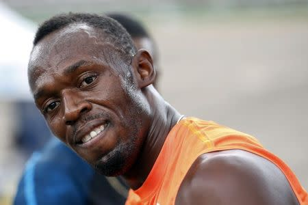 Jamaica's Usain Bolt smiles shortly after crossing the finish line first, in his first race of the season during the Gibson Relays in Kingston