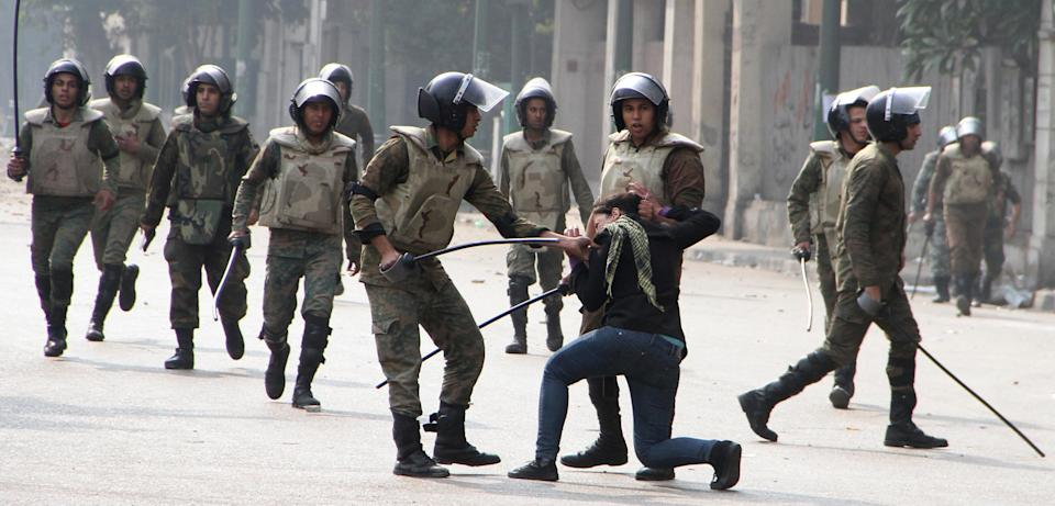 Egyptian army soldiers arrest a woman protester during clashes with military police near Cairo's downtown Tahrir Square, Friday, Dec. 16, 2011. Activists say the clashes began after soldiers severely beat a young man who was part of a sit-in outside the Cabinet building.  (AP Photo/Str)