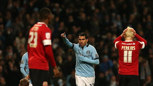 Carlos Tevez, centre, celebrates scoring Manchester City's fourth and his hat trick goal