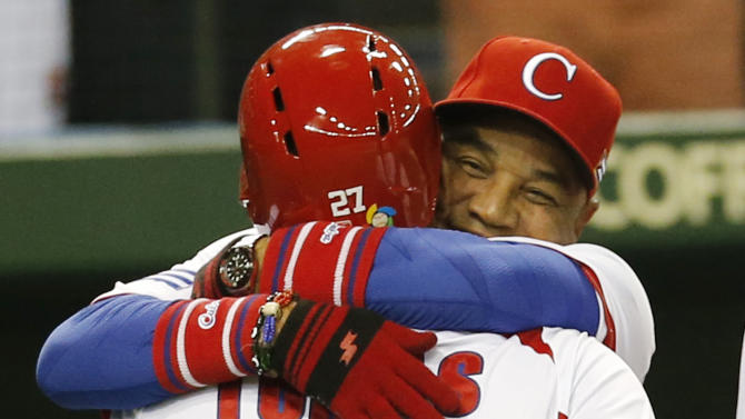 Cuba's rightfielder Yasmany Tomas (27) is hugged by manager Victor Mesa after hitting a three-run homer off Taiwan's pitcher Yang Yao-hsun in the fourth inning of their World Baseball Classic second round game at Tokyo Dome in Tokyo, Saturday, March 9, 2013. (AP Photo/Koji Sasahara)