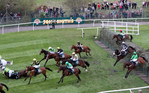 Synnchronized riden by Tony McCoy, left,  falls after jumping Becher's Brook during the Grand National at Aintree Racecourse, Liverpool, England, Saturday April 14, 2012. Pre-race favorite Synchronise