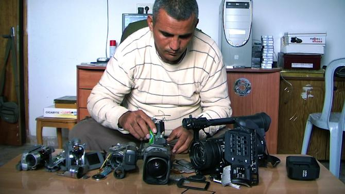 "FILE - This undated publicity photo released by Kino Lorber, Inc. shows Co-director Emad Burnat with his five broken cameras. Burnat and Guy Davidi co-directed the documentary film, ""5 Broken Cameras."" Immigration officials briefly detained the Palestinian director of the Oscar-nominated documentary ""5 Broken Cameras"" on his way into town for Sunday's Academy Awards. Burnat says that when he arrived at Los Angeles International Airport from Turkey with his wife and 8-year-old son late Tuesday, Feb. 19, 2013, he was told he didn't have the proper proof that he was a nominee.  (AP Photo/Kino Lorber, Inc, File.)"