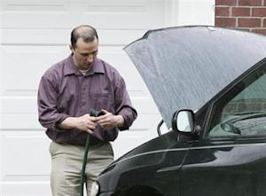 Everett Dutschke works on his mini-van in his driveway in Tupelo
