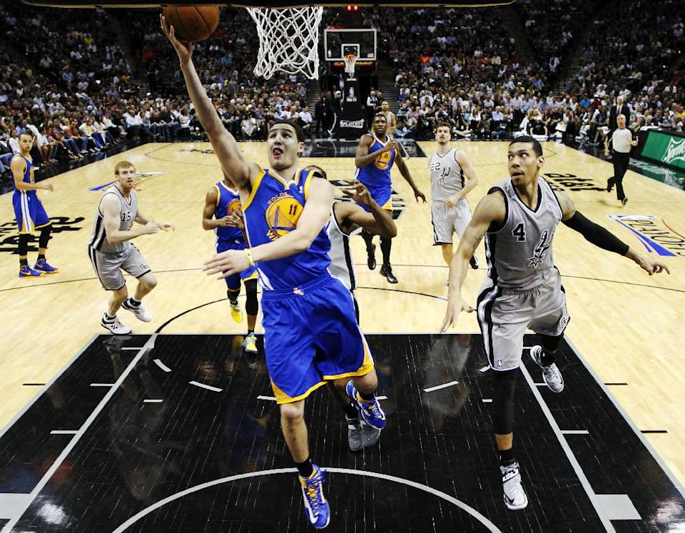 Golden State Warriors' Klay Thompson (11) scores as San Antonio Spurs' Danny Green (4) defends during the first half of Game 2 in their Western Conference semifinal NBA basketball playoff series, Wednesday, May 8, 2013, in San Antonio. (AP Photo/Eric Gay)