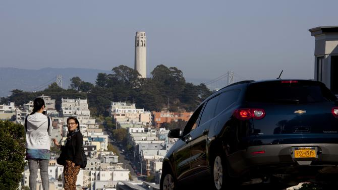 """In this photo taken Thursday, Sept. 27, 2012, people pose for pictures and a car makes its way down Lombard Street with Coit Tower on Telegraph Hill in the background in San Francisco. San Francisco has a long history as a favorite site for filmmakers and the movie buffs who want to see the spots where their favorite scenes took place, from Fort Point under the Golden Gate Bridge where Jimmy Stewart saved Kim Novak in """"Vertigo"""" to the steps of City Hall, where Sean Penn gave an impassioned speech in """"Milk,"""" to Alcatraz, stage for Clint Eastwood and many others. (AP Photo/Eric Risberg)"""