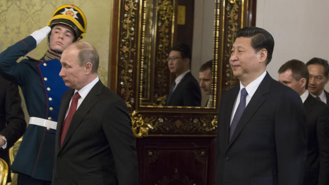 Russian President Vladimir Putin, left, and Chinese President Xi Jinping enter a hall before their talks in the Grand Kremlin Palace in Moscow, Russia, Friday, March 22, 2013. Russia is Xi Jinping's first foreign destination as China's president. Xi's talks with Putin on Friday are set to focus on oil and gas as China seeks to secure new energy resources to fuel its growing economy. (AP Photo/Alexander Zemlianichenko, Pool)