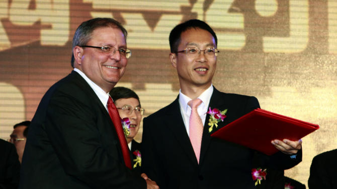 Gerry Lopez, CEO of AMC Entertainment Holdings, left, shakes hands with Zhang Lin, Vice President of Wanda during a signing ceremony for Dalian Wanda Group Co. to acquire AMC Entertainment Holdings in Beijing, China, Monday, May 21, 2012.  The Chinese conglomerate announced Monday it will buy major U.S. cinema chain, AMC Entertainment Holdings, for $2.6 billion to create the world's biggest movie theater operator. (AP Photo/Ng Han Guan)