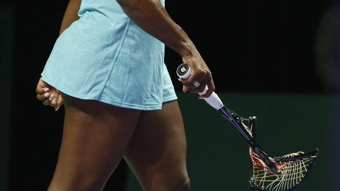 Serena Williams of the U.S. walks off the court with her second broken racquet during her WTA Finals singles semi-finals tennis match against Caroline Wozniacki of Denmark at the Singapore Indoor Stadium