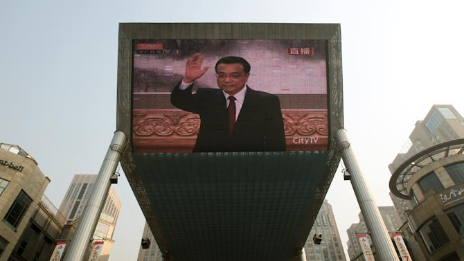 A huge TV screen shows a live broadcast of Li Keqiang, one of the seven newly elected members of the Politburo Standing Committee, waving during a press event, in Beijing Thursday Nov. 15, 2012. The seven-member Standing Committee, the inner circle of Chinese political power, was paraded in front of assembled media on the first day following the end of the 18th Communist Party Congress. (AP Photo/Andy Wong)