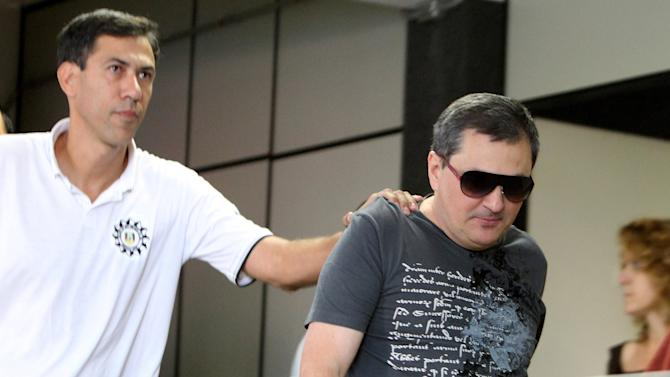 Mauro Hoffmann, right, co-owner of the Kiss nightclub, is escorted by police as he voluntarily surrenders at a police station in Santa Maria, Brazil, Monday, Jan. 28, 2013. A fast-moving fire roared through the crowded, windowless Kiss nightclub in this southern Brazilian city early Sunday, killing more than 230 people.  Brazilian police said they detained three other people in connection with the blaze. (AP Photo/Nabor Goulart)
