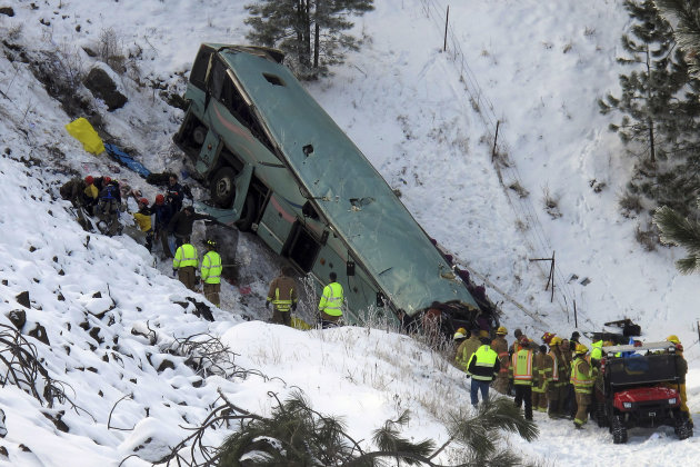 <p>               Emergency personnel respond to the scene of a multiple-fatality accident after a tour bus careened through a guardrail along an icy highway and fell several hundred feet down a steep embankment, authorities said, Sunday, Dec. 30, 2012 about 15 miles east of Pendleton, Ore. The charter bus carrying about 40 people lost control around 10:30 a.m. on the snow- and ice-covered lanes of Interstate 84, according to the Oregon State Police. (AP Photo/East Oregonian, Tim Trainor)