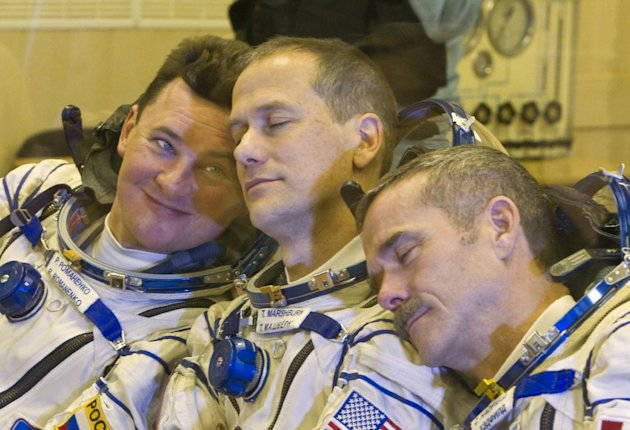 The International Space Station (ISS) crew members, from left: Russian cosmonaut Roman Romanenko, U.S. astronaut Thomas Marshburn and Canadian astronaut Chris Hadfield joke during their talk with relatives after putting on their space suits at the Baikonur cosmodrome Kazakhstan Wednesday, Dec. 19, 2012. (AP Photo/ Shamil Zhumatov, pool)