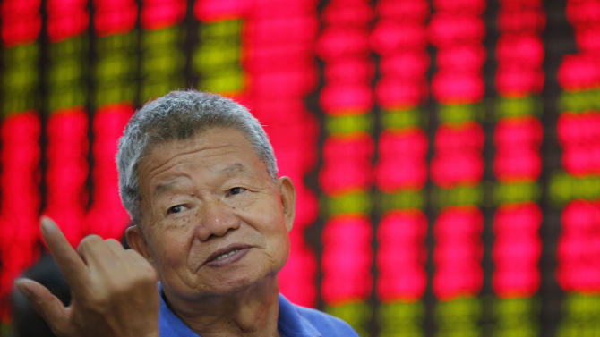 An investor gestures at a private securities company Monday Aug. 19, 2013 in Shanghai, China. Asian stock markets were little changed Monday as traders weighed the consequences of an anticipated phasing out of the U.S. central bank's unprecedented stimulus program. (AP Photo)