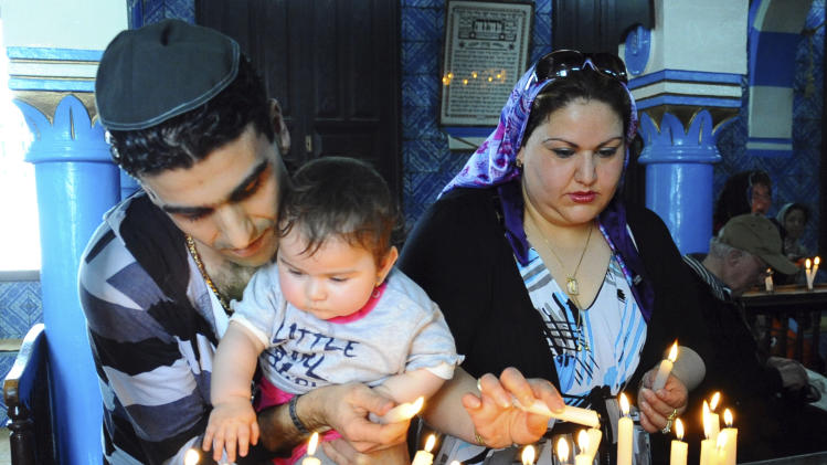 The French Jewish Zaaflani family light candles during the annual Jewish pilgrimage at the Ghriba synagogue in the resort of Djerba, Tunisia, Friday April 26, 2013. The pilgrimage to the synagogue commemorates the April 11, 2002 deadly attack on the synagogue that killed 21 people, including 14 German tourists. (AP Photo/Hassene Dridi)