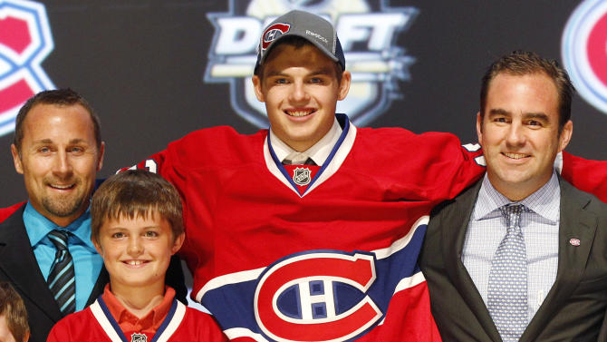 Alex Galchenyuk, center, smiles with officials from the Montreal Canadiens after being chosen third overall in the first round of the NHL hockey draft on Friday, June 22, 2012, in Pittsburgh. (AP Photo/Keith Srakocic)