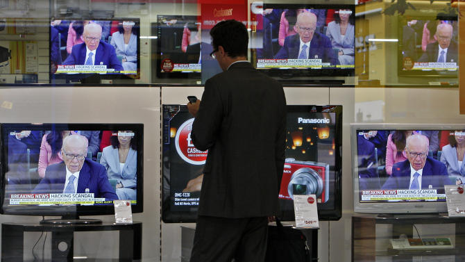 A pedestrian looks at his cell phone as he stops by television screens, showing Chairman of News Corporation Rupert Murdoch during a select committee on the phone hacking scandal, outside a electronics shop in London, Tuesday, July 19, 2011. (AP Photo/Akira Suemori)