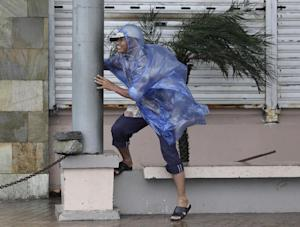 A man holds on to a pole as strong winds blow brought …
