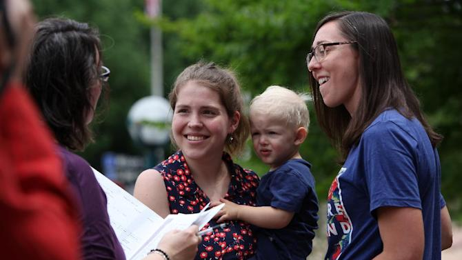 Rose Grindrod, center, gets married to Meghan Hamilton, as she hold their son Harry Hamilton, outside the City-County Building the day after the ban on same-sex marriage was struck down in Wisconsin, in Madison, Wis., Saturday, June 7, 2014. Dozens of gay couples married Saturday at courthouses in Milwaukee and Madison, taking advantage of what most believed would be a small window in which to get hitched before a judge's decision overturning the state's same-sex marriage ban was put on hold. (AP Photo/Wisconsin State Journal, Amber Arnold)