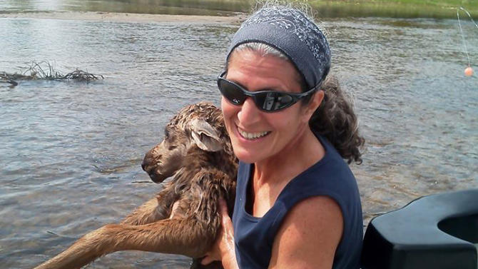This image provided by the Four Rivers Fishing Co., shows Karen Sciascia of Red Hill, Pa., holding a baby moose she and Twin Bridges guide Seth McLean rescued in the Big Hole River in southwestern Montana on Saturday, June 1, 2013, near Missoula, Mont. Sciascia says she scooped the moose out of the water and McLean rowed the raft upriver so they could return the calf to her mother. (AP Photo/Four Rivers Fishing Co.)