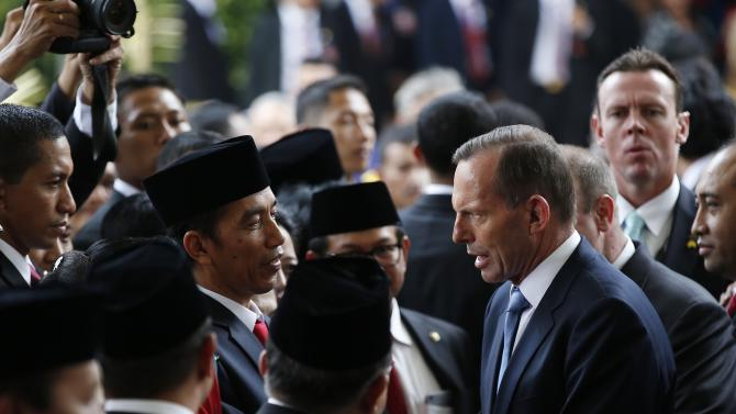 Indonesia's new President Widodo shakes hands with Australia's Prime Minister Abbott  after Widodo's inuaguration in Jakarta