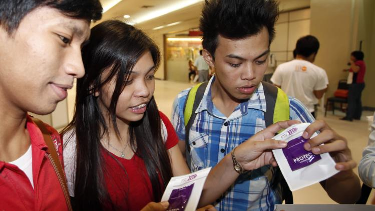 Students receive free condoms at an event organised by the United Nations Population Fund on World Population Day in Mandaluyong