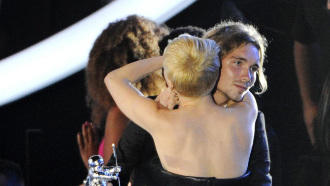 FILE - In this Sunday, Aug. 24, 2014 file photo, Miley Cyrus, front, hugs Jesse Helt, right, at the MTV Video Music Awards at The Forum in Inglewood, Calif. The young homeless man who accompanied Cyrus to the MTV Video Music Awards has a warrant out for his arrest in Oregon. Helt gained worldwide attention Sunday when Cyrus let him accept her award for video of the year. (Photo by Chris Pizzello/Invision/AP, file)