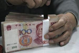An employee seals a stack of yuan banknotes at a branch …