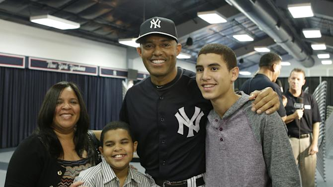 New York Yankees pitcher Mariano Rivera, who holds baseball's all-time saves record, poses for a photograph with his wife Clara, sons Jaziel, left, and Jafet, right, after  announcing his plans to retire at the end of the 2013 season during a news conference at Steinbrenner Field Saturday, March 9, 2013 in Tampa, Fla. (AP Photo/Kathy Willens)