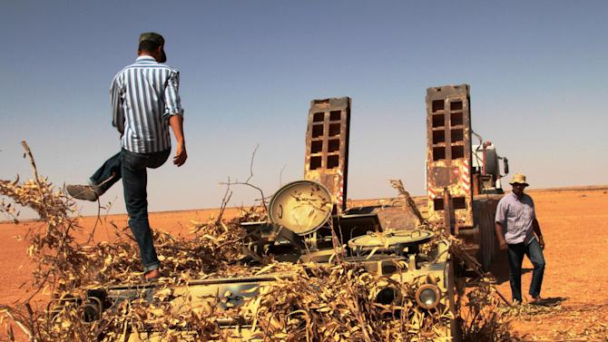 Rebel  fighters take control of  a military vehicle positioned to defend what used to be Gadhafi's 32nd infantry regiment's base at Mardun, some 10 kilometers from the outskirts of Ban Walid, Libya, Wednesday, Sept. 7, 2011. (AP Photo/Gaia Anderson)