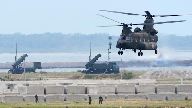A Japan Self-Defense Force helicopter takes off near ground-based Patriot Advanced Capability-3 interceptors set up on alert against North Korea's planned rocket launch Tuesday, Dec. 11, 2012 in Ishigaki, Okinawa Prefecture, southwestern Japan. North Korea is pressing ahead with preparation for a long-range rocket launch after extending its liftoff window by another week until Dec. 29 because of technical problems. (AP Photo/Kyodo News) JAPAN OUT, MANDATORY CREDIT, NO LICENSING IN CHINA, FRANCE, HONG KONG, JAPAN AND SOUTH KOREA