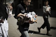 A Syrian man carries his wounded daughter outside a hospital in the northern city of Aleppo on September 18. Syrian rebels seized a crossing on the Turkish border Wednesday even as they quit a swathe of south Damascus that activists said had been reduced to a disaster area by weeks of heavy fighting