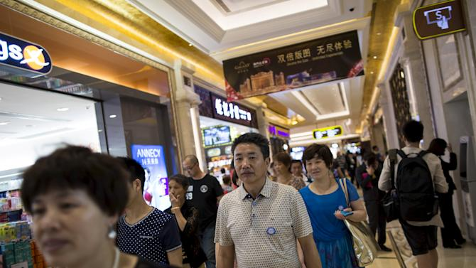 Tourists walk inside a shopping mall at Galaxy Macau resort in Macau