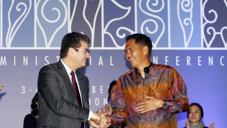 Indonesian Trade Minister Gita Wiryawan, right, shakes hands with World Trade Organization (WTO) Director-General Roberto Azevedo during the closing ceremony of the ninth WTO Ministerial Conference in Bali, Indonesia, Saturday, Dec. 7, 2013. (AP Photo/Firdia Lisnawati)