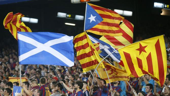 """Catalunya's separatist supporters wave """"Esteladas"""" supporting Scotland's independence during FC Barcelona's Champions League soccer match against Apoel Nicosia in Barcelona"""