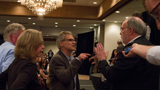 """CORRECTS SPELLING OF LAST NAME TO DOVE INSTEAD OF DOBB - In this photo provided by Jacob Green, a man who identified himself as Missoula attorney Thomas Dove, right, elbows his way to the stage at a forum open to the public Wednesday night, May 6, 2015, accusing author John Krakauer, center, of lying and using confidential documents in his book """"Missoula: Rape and the Justice System in a College Town, """" in Missoula, Mont., where Krakauer came to address the concerns of critics after the book's publication on April 21.  (Jacob Green via AP)"""
