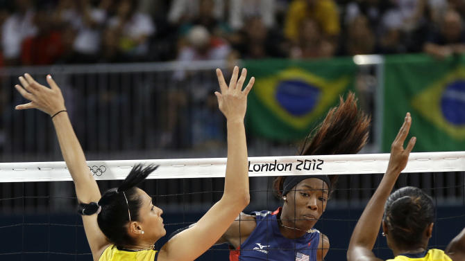 USA's Destinee Hooker (19) watches her spike get past Brazil's Jaqueline Carvalho (8) and Fabiana Claudino (1) during a women's volleyball gold medal match at the 2012 Summer Olympics Saturday, Aug. 11, 2012, in London. (AP Photo/Chris O'Meara)