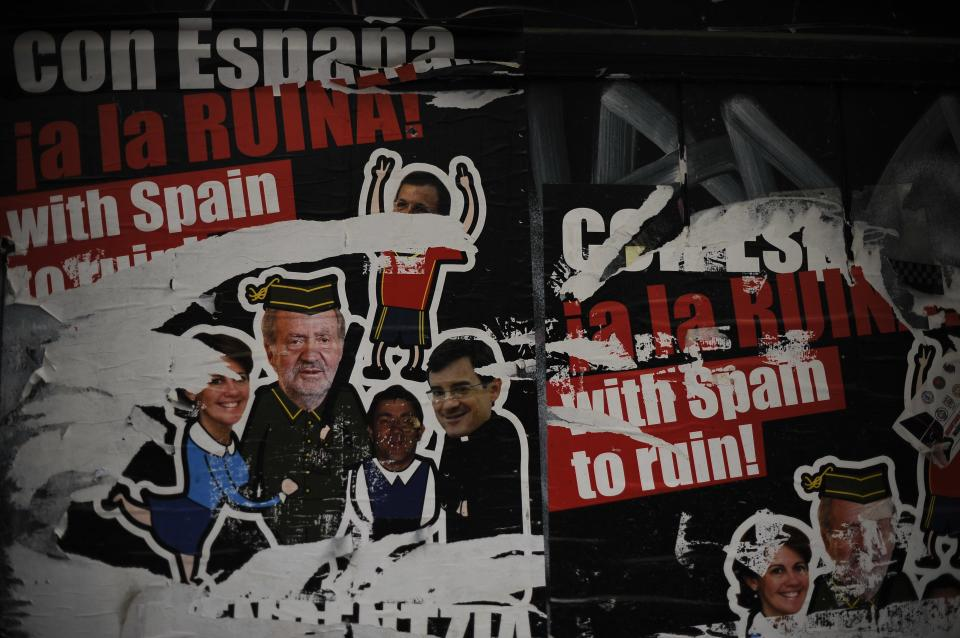 Posters against Spanish King Juan Carlos, left and bottom right, seen on a wall reading, ''With Spain to ruin'', during the celebration of the day of workers, May Day, in Pamplona, northern Spain on Wednesday, May 1, 2013.  (AP Photo/Alvaro Barrientos)