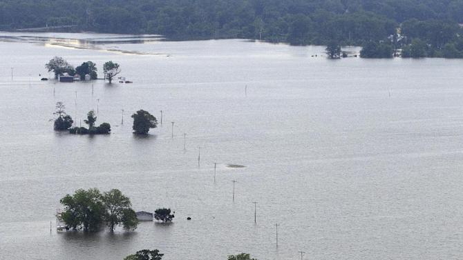 FILE - In this May 19, 2011 file photo, a row of flooded farm homes are pictured near Yazoo City, Miss. Inspectors taking the first-ever inventory of flood control systems overseen by the federal government have found hundreds of structures at risk of failing and endangering people and property in 35 states. Levees deemed in unacceptable condition span the breadth of America. They are in every region, in cities and towns big and small: Washington, D.C. (AP Photo/Dave Martin, File)