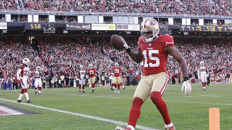 San Francisco 49ers wide receiver Michael Crabtree (15) scores on a 7-yard touchdown reception from quarterback Colin Kaepernick during the third quarter of an NFL football game against the Arizona Cardinals in San Francisco, Sunday, Dec. 30, 2012. (AP Photo/Tony Avelar)